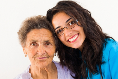 an elderly woman with her personal nurse smiling together in front of the camera