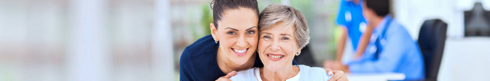 an elderly woman and a caregiver smiling together in front of the camera