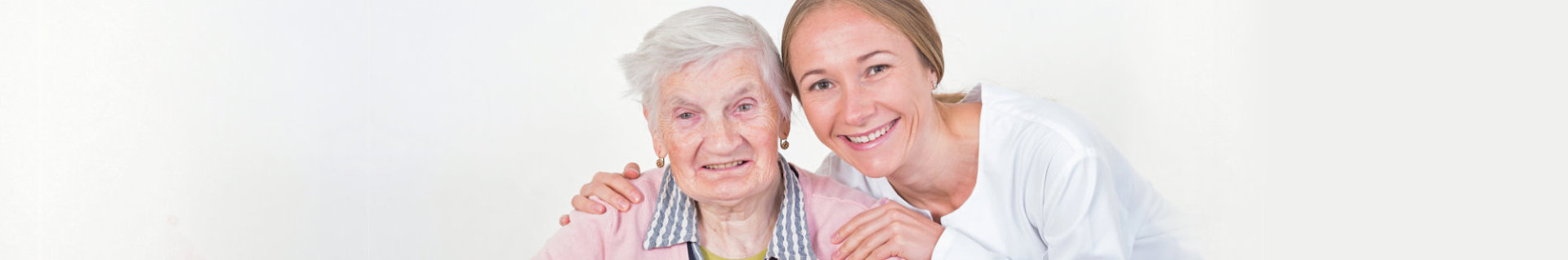 an elderly woman with her caregiver smiling together