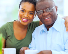 daughter and her father drinking coffee and smiling in front of the camera
