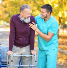 an elderly man assisted by his caregiver to walk