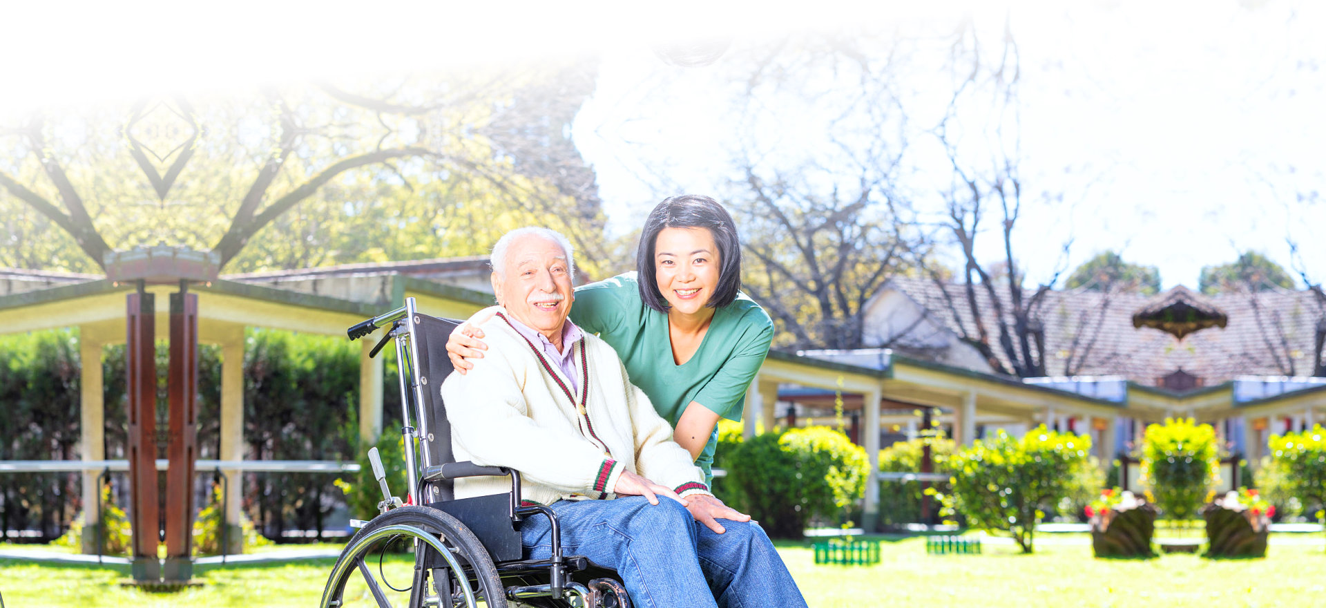 caregiver and her patient in wheelchair looking at camera while smiling