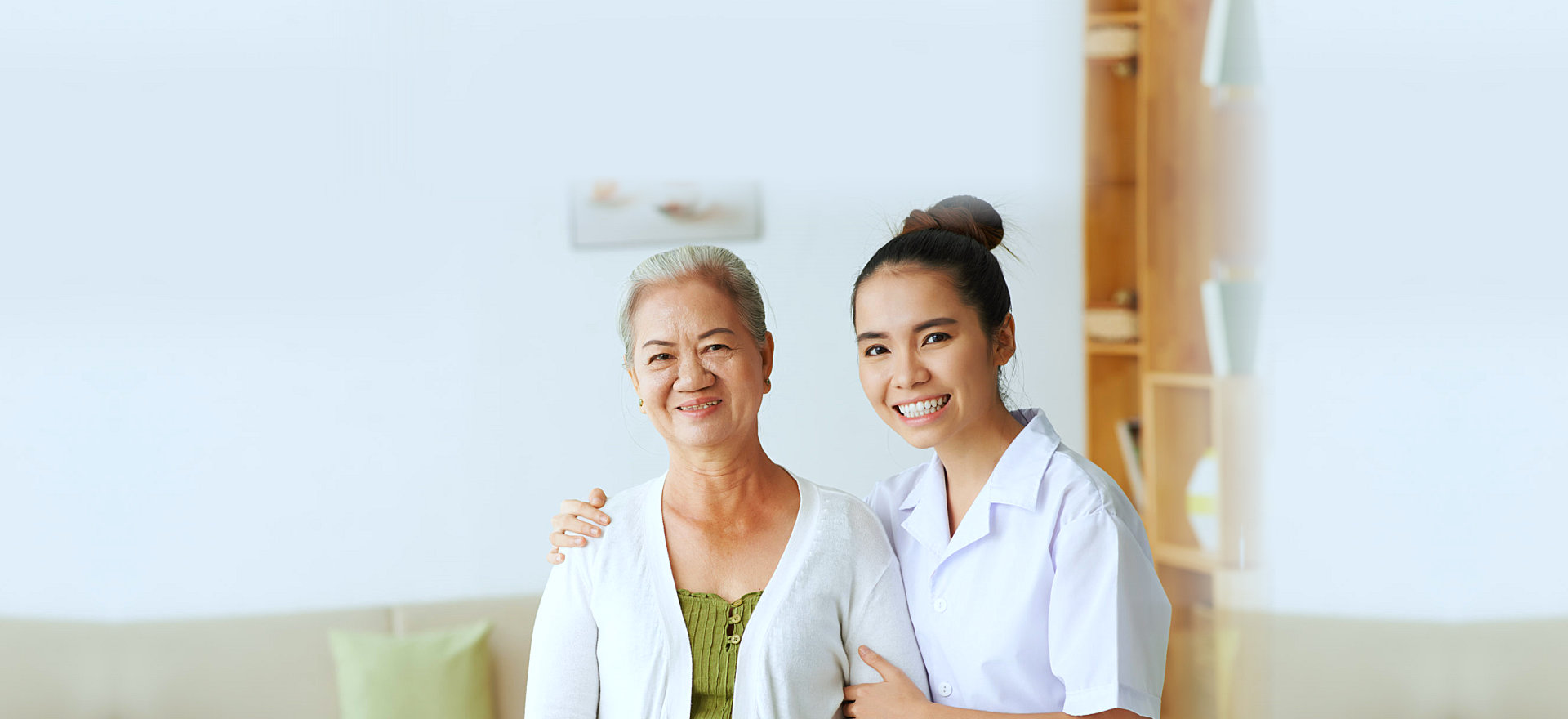 an elderly woman and her caregiver smiling
