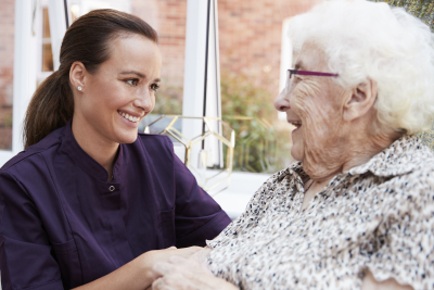 an elderly woman with her caregiver smiling each other